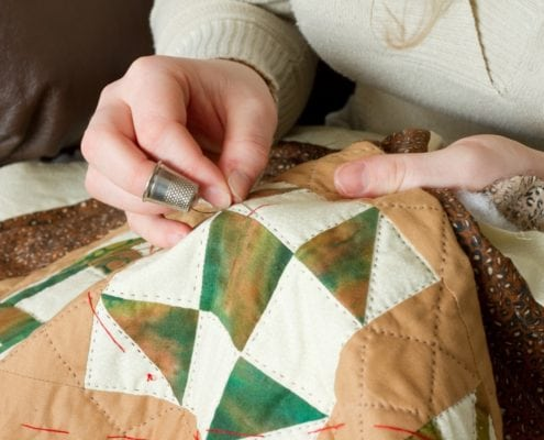 Young Woman's Hands with Thimble and Sewing Needle Quilting