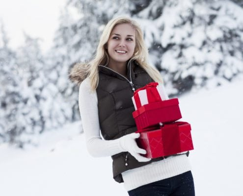 Beautiful Young Woman Smiling, Carrying Christmas Gifts in Snow
