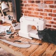 Desk of fashion designer with sewing machine and tools
