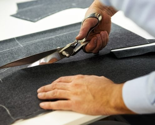 Tailor cutting fabric with large scissors