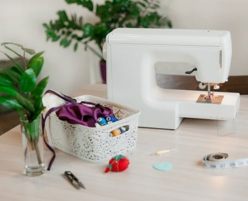 Light minimalist work space for tailor. White sewing machine and basket of sewing accessories on a table. Green house plants in seamstress working place. Concept of female small business at home.