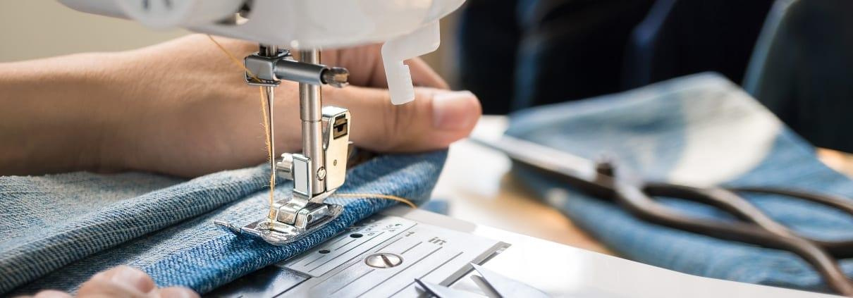 women's hand working on sewing machine