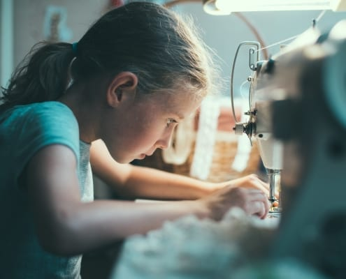 Little girl working on sewing machine