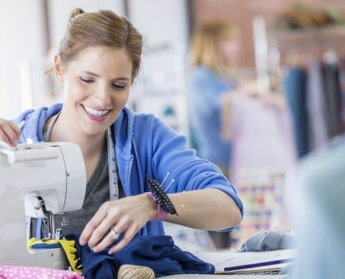 happy woman uses a sewing machine